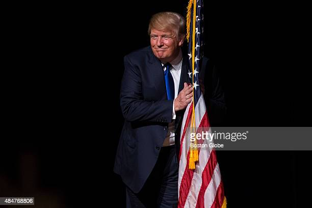 S Republican presidential candidate Donald Trump hugs an American flag as he takes the stage for a town hall meeting in Derry New Hampshire August 19...