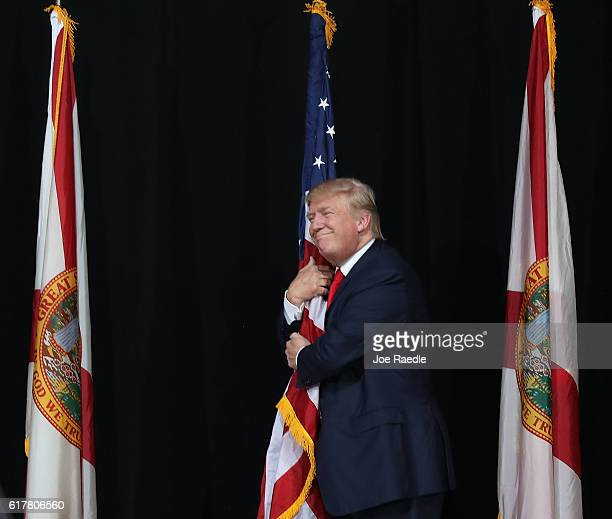 Republican presidential candidate Donald Trump hugs the American flag as he arrives for a campaign rally at the MidFlorida Credit Union Amphitheatre...