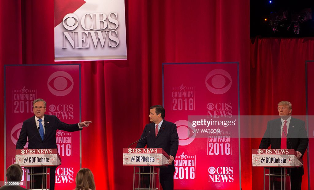 Republican presidential candidate Donald Trump (R) listens as Jeb Bush (L) gestures as they argue through Ted Cruz (C) during the CBS News Republican Presidential Debate in Greenville, South Carolina, February 13, 2016. / AFP / JIM WATSON