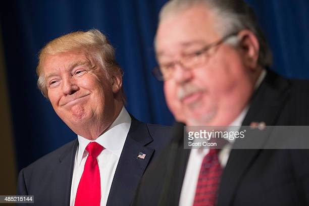 Republican presidential candidate Donald Trump listens as Sam Clovis speaks at a press conference at the Grand River Center on August 25 2015 in...