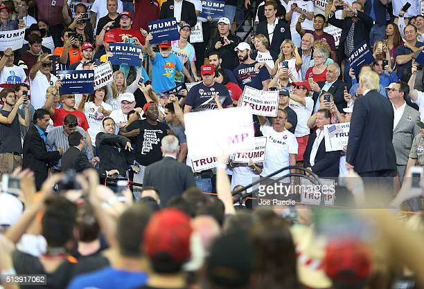 Republican presidential candidate Donald Trump looks on at protesters yelling at him during his campaign rally at the CFE Arena on the campus of the...