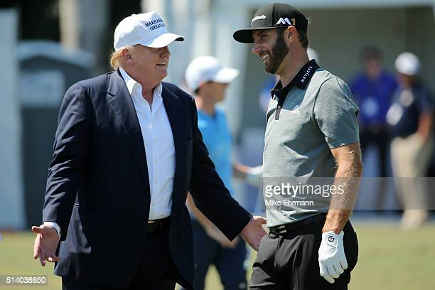 Republican presidential candidate Donald Trump makes an appearance prior to the start of play and speaks with golfer Dustin Johnson on the range...