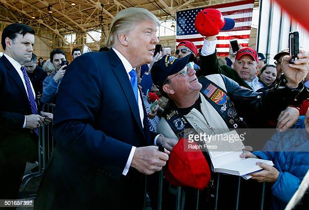 Republican presidential candidate Donald Trump poses for a picture with a supporter during a campaign event at the International Air Response...