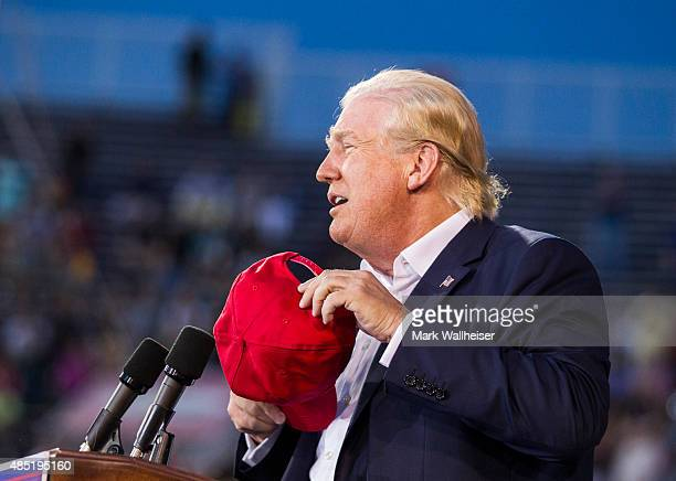 S Republican presidential candidate Donald Trump removes his hat to show that his hair is real during a political rally at LaddPeebles Stadium on...