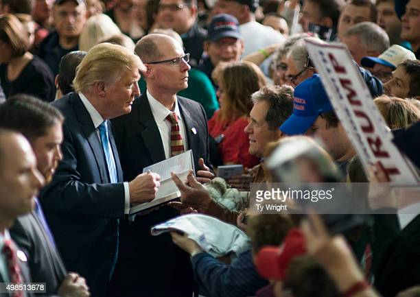 Republican Presidential candidate Donald Trump shakes hands and signs autographs with his supporters after speaking at a campaign rally at the...