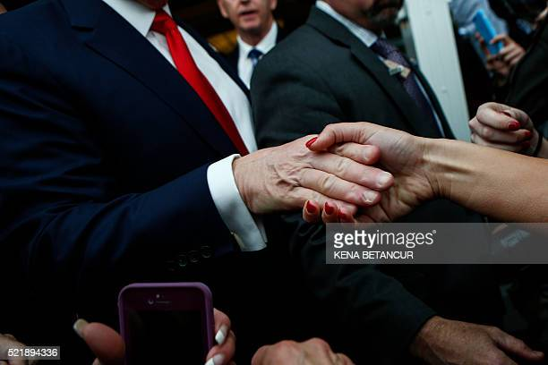 Republican presidential candidate Donald Trump shakes hands with a supporter at the end of a press conference with members of the New York Veteran...
