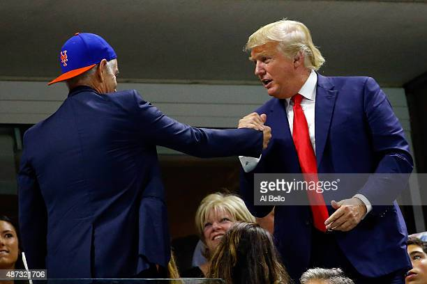 Republican presidential candidate Donald Trump shakes hands with former tennis player John McEnroe attend the Women's Singles Quarterfinals match...