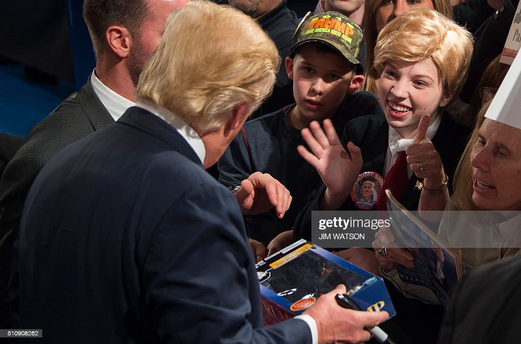 Republican presidential candidate Donald Trump signs a Trump doll for a girl dressed in costume like him during a campaign rally in Sumter, South Carolina, February 17, 2016. / AFP / JIM