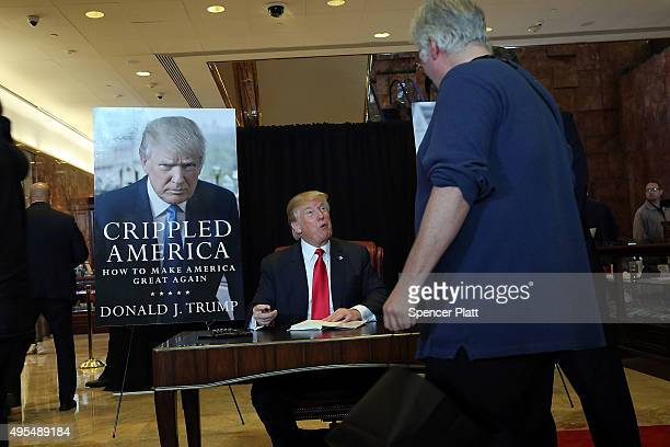 Republican presidential candidate Donald Trump sign's his new book 'Crippled America How to Make America Great Again' at the Trump Tower Atrium on...