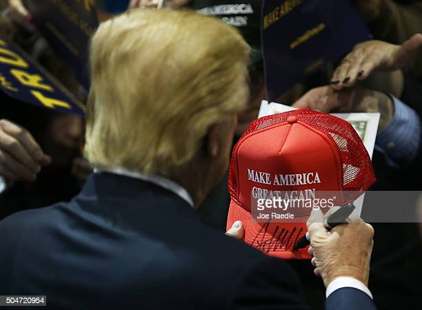 Republican presidential candidate Donald Trump signs one of his campaign hats during a event at the University of Northern Iowa on January 12 2016 in...