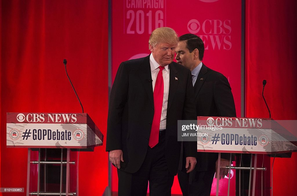 Republican presidential candidate Donald Trump (L) speaks with Marco Rubio (R) during the CBS News Republican Presidential Debate in Greenville, South Carolina, February 13, 2016. / AFP / JIM WATSON