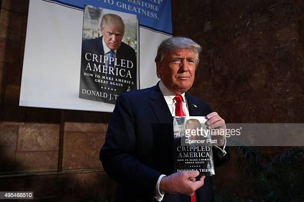 Republican presidential candidate Donald Trump stands with his new book 'Crippled America How to Make America Great Again' before a public signing...