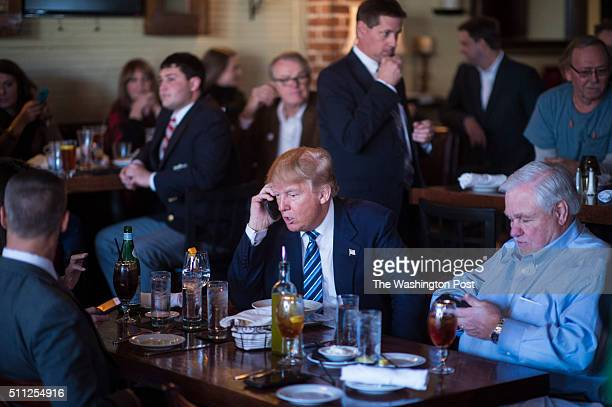Republican presidential candidate Donald Trump talks talks on the phone while making a stop for lunch between campaign events at Fratello's Italian...