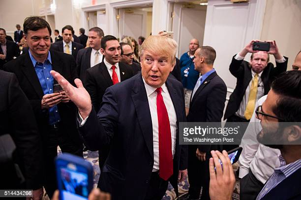 Republican presidential candidate Donald Trump talks with reporters before speaking at a campaign press conference event at the Trump National Golf...