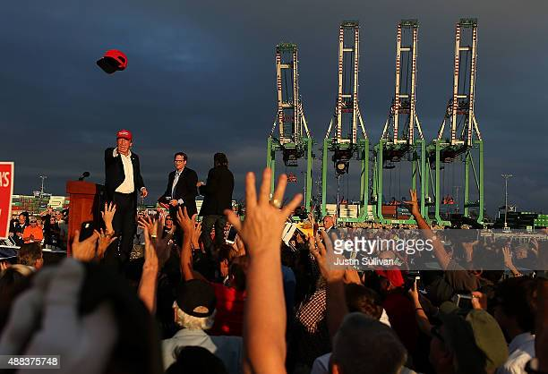 Republican presidential candidate Donald Trump throws a hat to supporters during a campaign rally aboard the USS Iowa on September 15 2015 in Los...