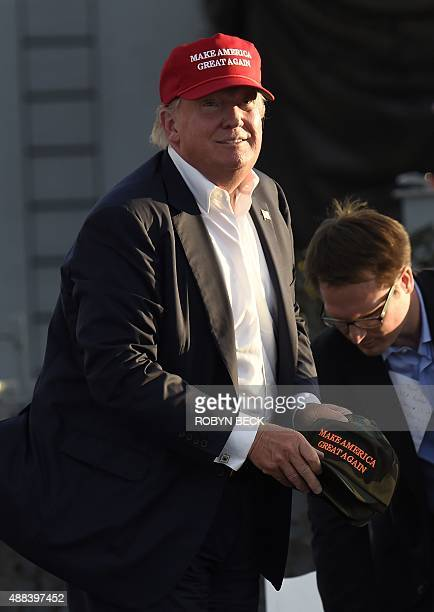 Republican presidential candidate Donald Trump throws hats into the audience after giving a speech aboard the World War II Battleship USS Iowa...