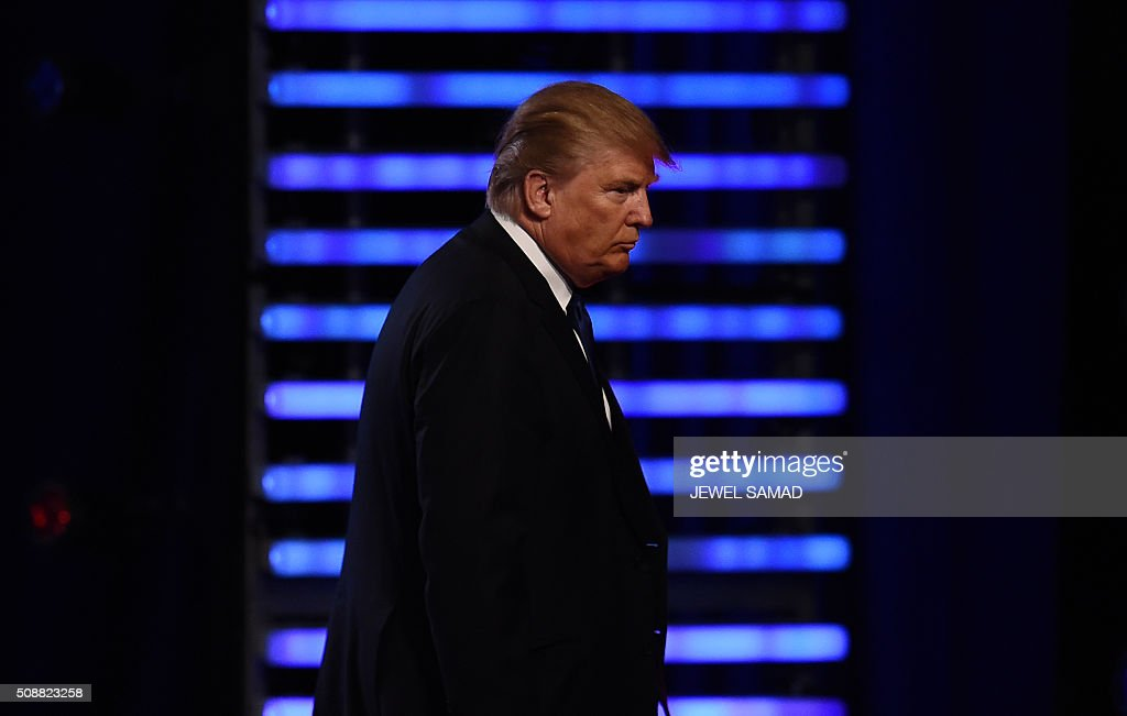 Republican presidential candidate Donald Trump walks across the stage following the Republican Presidential Candidates Debate on February 6, 2016 at St. Anselm's College Institute of Politics in Manchester, New Hampshire. Seven Republicans campaigning to be US president are in a fight for survival in their last debate Saturday before the New Hampshire primary, battling to win over a significant number of undecided voters. / AFP / Jewel Samad