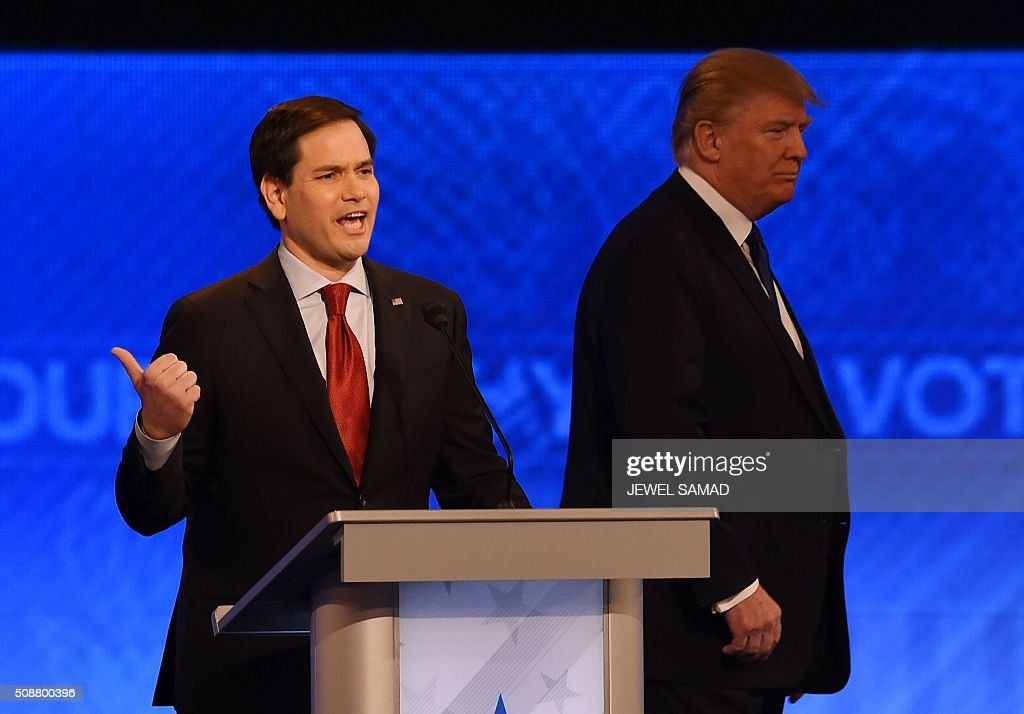 Republican presidential candidate Donald Trump (R) walks past fellow candidate Marco Rubio (L) prior to the start of the Republican Presidential Candidates Debate on February 6, 2016 at St. Anselm's College Institute of Politics in Manchester, New Hampshire. Seven Republicans campaigning to be US president are in a fight for survival in their last debate Saturday before the New Hampshire primary, battling to win over a significant number of undecided voters. / AFP / Jewel Samad