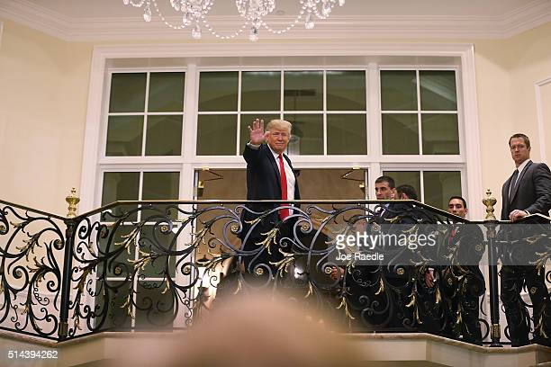 Republican presidential candidate Donald Trump waves to people from a balcony after holding a press conference at the Trump National Golf Club...