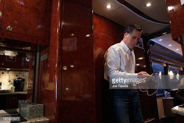 Republican presidential candidate former Massachusetts Gov Mitt Romney dictates an email using Siri on his iPhone as he rides on his campaign bus...