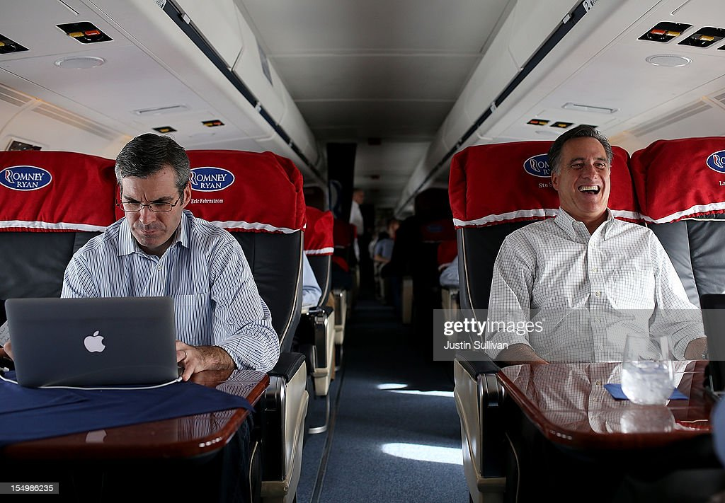 Republican presidential candidate, former Massachusetts Gov. Mitt Romney (R) laughs as his senior advisor and spokesman Kevin Madden (L) works on his laptop on his campaign plane October 29, 2012 en route to Moline, Illinois. Romney canceled campaign events on October 29 and 30 due to Hurricane Sandy.