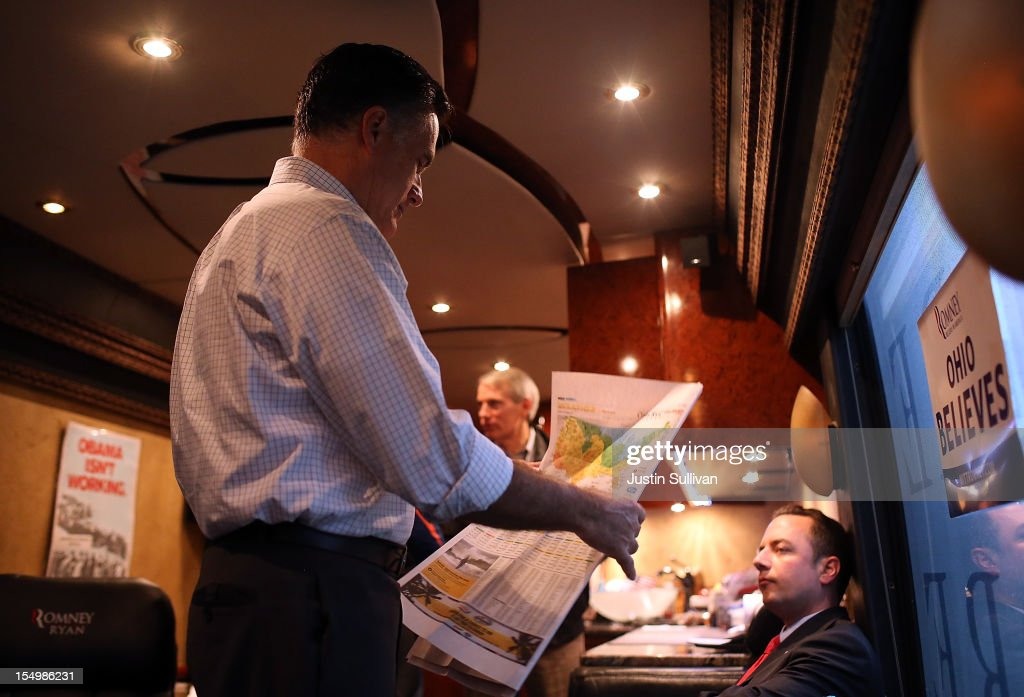 Republican presidential candidate, former Massachusetts Gov. Mitt Romney looks at the weather report in a newspaper on his campaign bus en route to a campaign rally at Avon Lake High School on October 29, 2012 in Avon Lake, Ohio. Romney canceled campaign events on October 29 and 30 due to Hurricane Sandy.