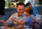 Republican presidential candidate former Massachusetts Gov Mitt Romney plays with his grandson Parker Romney while having dinner at BurgerFi on...