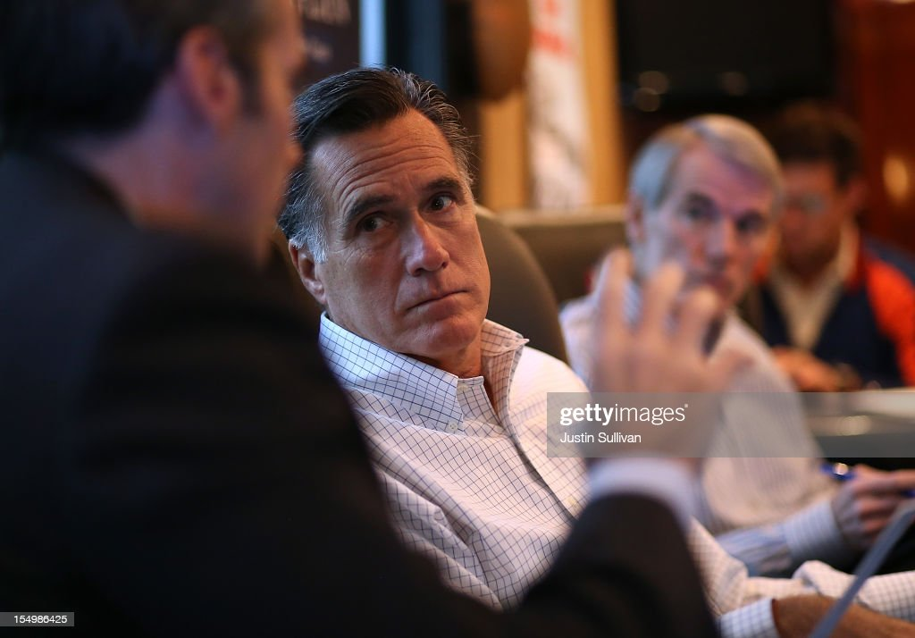 Republican presidential candidate, former Massachusetts Gov. Mitt Romney (C) talks with senior advisor and campaign spokesman Kevin Madden (L) on his campaign bus en route to a campaign rally at Avon Lake High School on October 29, 2012 in Avon Lake, Ohio. Romney canceled campaign events on October 29 and 30 due to Hurricane Sandy.