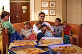 Republican presidential candidate former Massachusetts Gov Mitt Romney sits in his hotel room with his grandchildren as he watches a television...