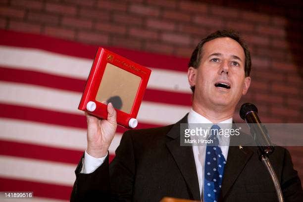 Republican presidential candidate former US Sen Rick Santorum holds up an EtchASketch as he speaks to supporters at a 'Rally for Rick' at Ledgeview...