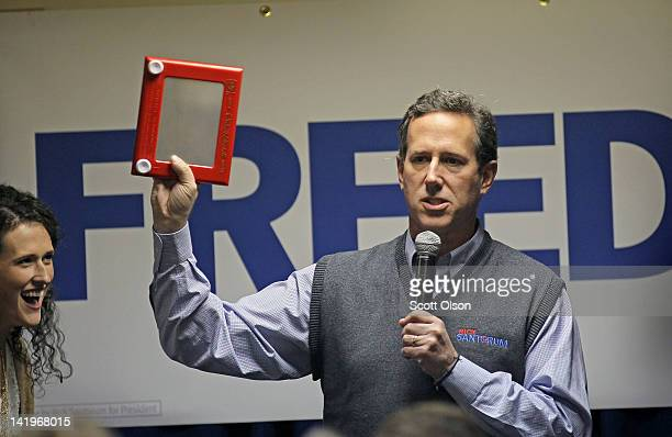 Republican presidential candidate former US Sen Rick Santorum holds an Etch a Sketch while speaking to guests gathered for a campaign rally on March...