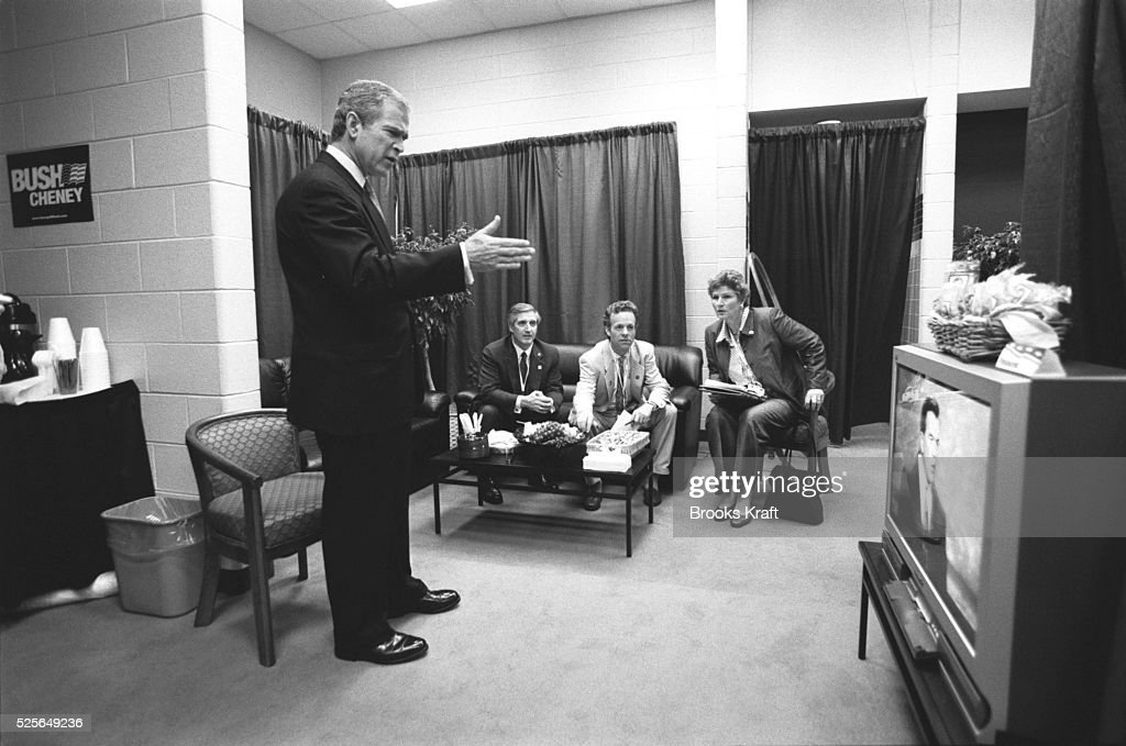 Republican presidential candidate George W Bush reacts to speeches shown on a TV as he waits with advisors Mark McKinnon and Karen Hughes Bush was...