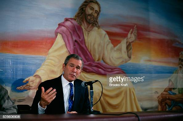 Republican presidential candidate George W Bush speaks in front of a mural of Jesus Christ in the basement of a church at the Teen Challenge of the...