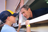 Republican presidential candidate George W Bush takes a food order from a child at an ice cream stand on July 4th in New Hampshire | Location Amherst...