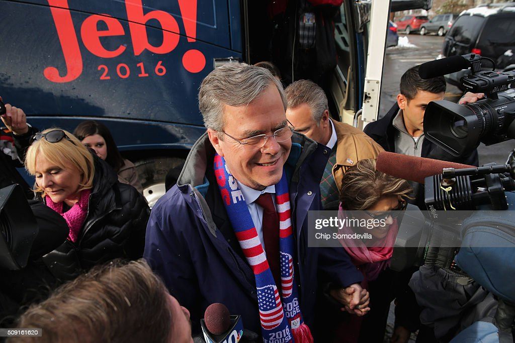Republican presidential candidate Jeb Bush and his wife Columba Bush wade into a crowd of television cameras after stepping off his campaign bus outside the polling place at Webster School on primary day February 9, 2016 in Manchester, New Hampshire. Candidates from both parties are making last-minute attempts to swing voters to their side on the day of the 'First in the Nation' presidential primary.