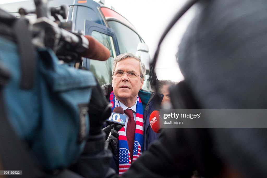 Republican presidential candidate Jeb Bush talks to media after stepping off his campaign bus outside the polling place at Webster School on primary day February 9, 2016 in Manchester, New Hampshire. Candidates from both parties are making last-minute attempts to swing voters to their side on the day of the 'First in the Nation' presidential primary.