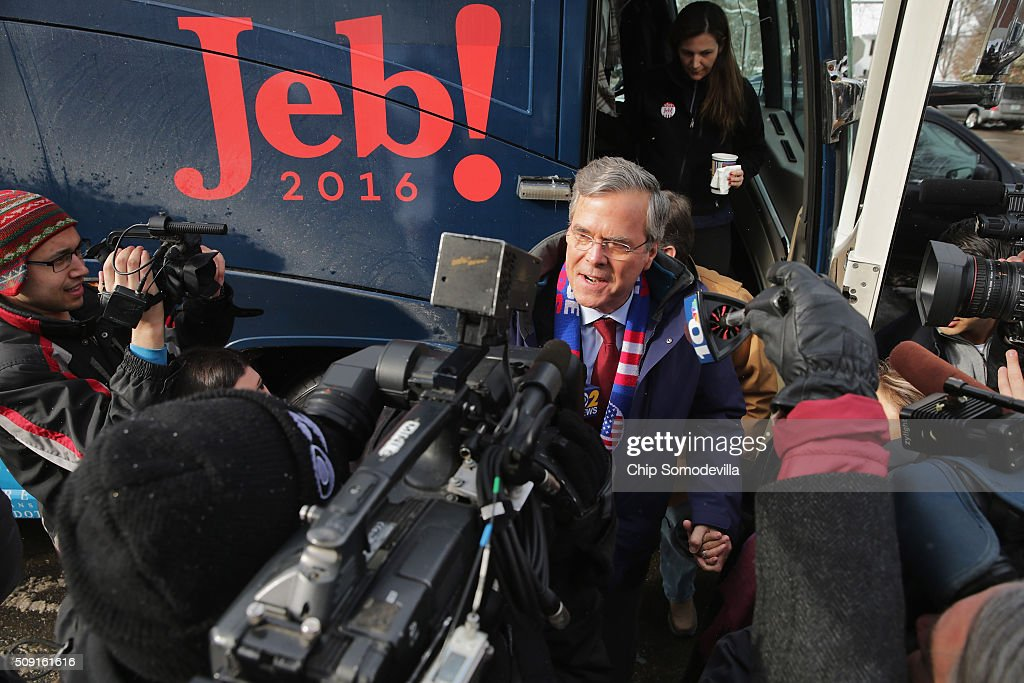 Republican presidential candidate Jeb Bush wades into a crowd of television cameras after stepping off his campaign bus outside the polling place at Webster School on primary day February 9, 2016 in Manchester, New Hampshire. Candidates from both parties are making last-minute attempts to swing voters to their side on the day of the 'First in the Nation' presidential primary.