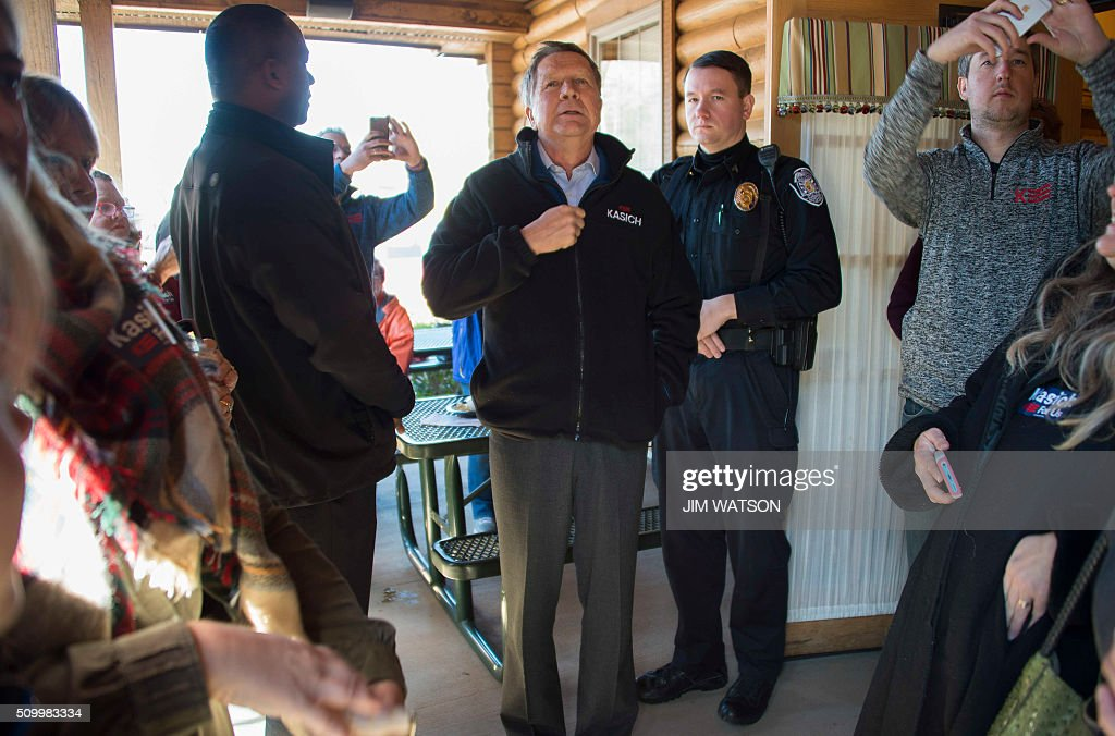 Republican presidential candidate John Kasich (C) adjusts his jacket as he waits back stage before speaking outside Mutt's BBQ in Mauldin, South Carolina, February 13, 2016. / AFP / JIM WATSON