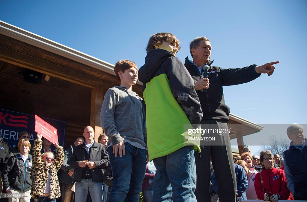 Republican presidential candidate John Kasich brings some children on stage as he speaks outside Mutt's BBQ in Mauldin, South Carolina, February 13, 2016. / AFP / JIM WATSON