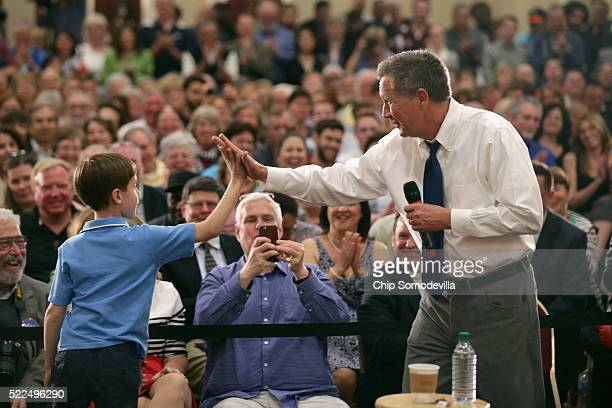 Republican presidential candidate John Kasich gives a highfive to a boy who joined him on stage during a campaign town hall meeting in the ballroom...