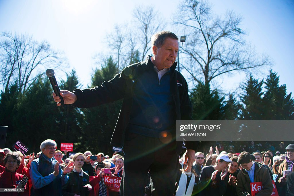 Republican presidential candidate John Kasich holds out his microphone as he finishes speaking outside Mutt's BBQ in Mauldin, South Carolina, February 13, 2016. / AFP / JIM WATSON