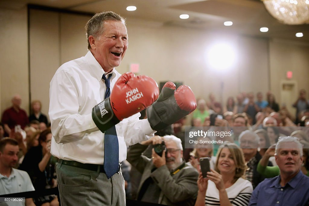 Republican presidential candidate John Kasich puts on a pair of boxing gloves given to him by a supporter during a campaign town hall meeting in the...