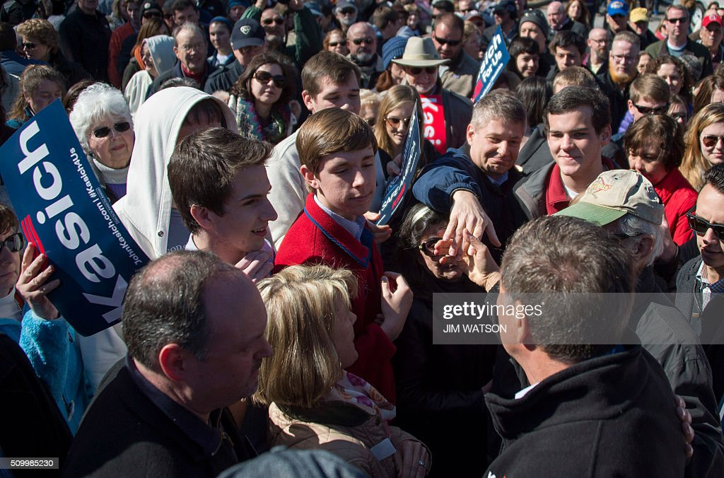 Republican presidential candidate John Kasich (R) shakes hands with supporters after speaking outside Mutt's BBQ in Mauldin, South Carolina, February 13, 2016. / AFP / JIM WATSON