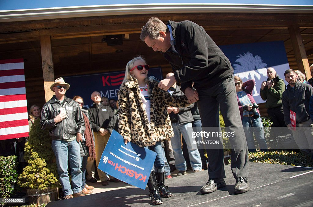Republican presidential candidate John Kasich (R) speaks with a young supporter, 7-year-old Ginny Hoddy, during a campaign rally outside Mutt's BBQ in Mauldin, South Carolina, February 13, 2016. / AFP / JIM WATSON