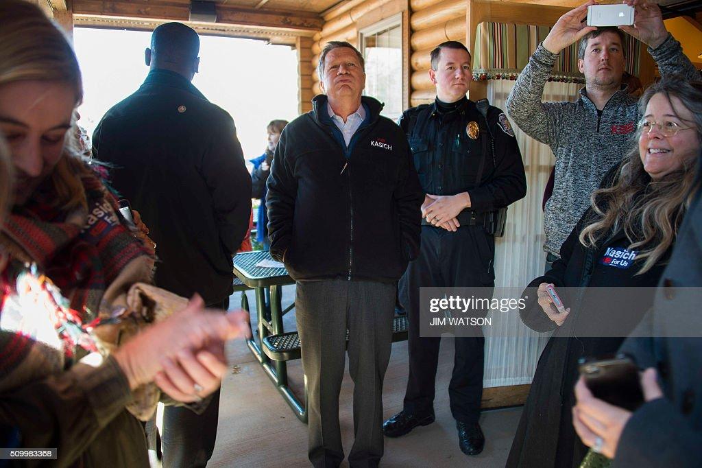 Republican presidential candidate John Kasich (C) waits before speaking outside Mutt's BBQ in Mauldin, South Carolina, February 13, 2016. / AFP / JIM WATSON