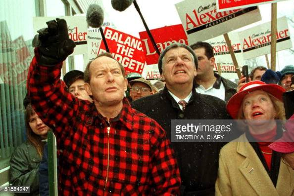 Republican Presidential candidate Lamar Alexander waves to supporters as he tours downtown Milford New Hampshire 14 February with former Education...
