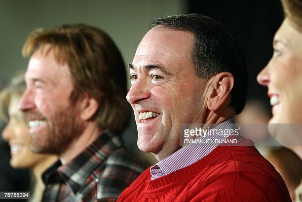 US Republican presidential candidate Mike Huckabee smiles while attending with his wife Janet and actor Chuck Norris a political meeting in...