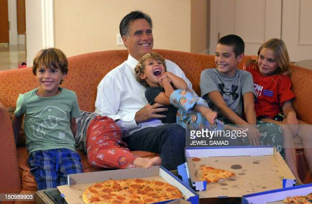 US Republican presidential candidate Mitt Romney along with his grandchildren watches the Republican National Convention on television in their hotel...