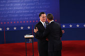 Republican presidential candidate Mitt Romney and US President Barack Obama shake hands prior to the start of a town hall style debate at Hofstra...