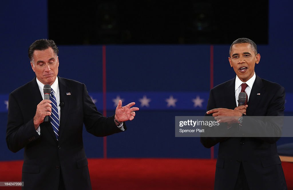 Republican presidential candidate Mitt Romney and US President Barack Obama both talk the audience during a town hall style debate at Hofstra...
